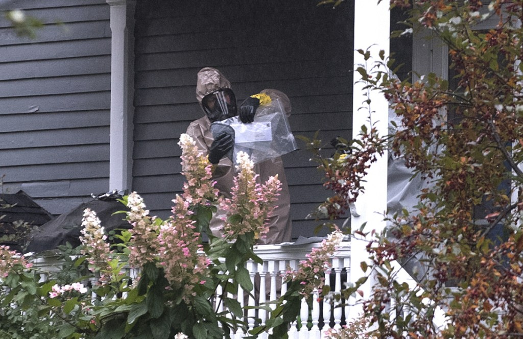 A person in a hazmat suit appears to be handling a letter that is enclosed in a plastic bag in Bangor on Monday. A hazardous materials team was called to investigate a suspicious letter sent to the home of Republican Sen. Susan Collins, officials said.
