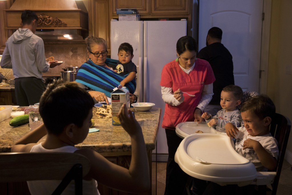 In this Thursday, Sept. 6, 2018, photo, Lilia Coyt, center left, and Coyt's daughter-in-law, Araceli Nunez, feed babies in their four-bedroom home, where three generations and 15 members of the family are jammed into, in Salinas, Calif. Few cities exemplify California's housing crisis better than Salinas, an hour's drive from Silicon Valley and surrounded by farm fields. It's one of America's most unaffordable places to live, and many residents believe politicians lack a grip on the reality of the region's housing crisis.