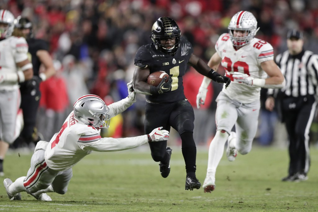 Purdue running back D.J. Knox cuts between Ohio State safety Jordan Fuller (4) and linebacker Pete Werner on his way to a touchdown Saturday.