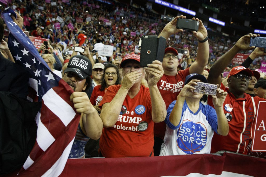 Supporters of President Trump cheer as he arrives for a rally for Sen. Ted Cruz, R-Texas, at Houston Toyota Center on Monday in Houston.