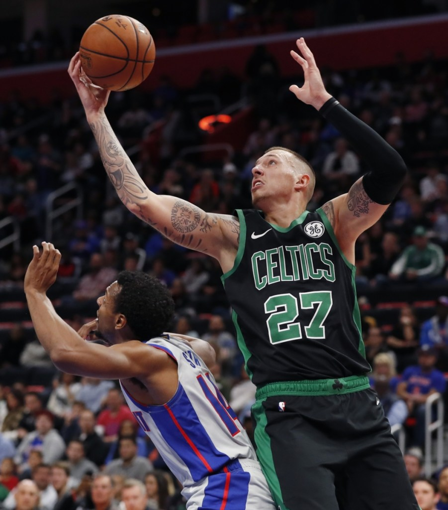 Daniel Theis of the Celtics leaps over Pistons guard Ish Smith to catch a pass Saturday during Boston's 109-89 win. Associated Press/Carlos Osorio