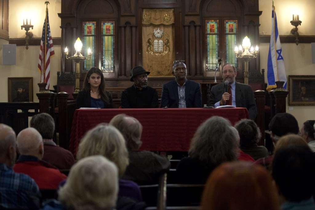 Rabbi David Fox Sandmel, right, reads the names of the victims of the shooting at the Tree of Life synagogue in Pittsburgh before hosting a panel with Amy Feinman, left, Pious Ali, Damas Rugaba at the Maine Jewish Museum in Portland on Sunday. (Staff Photo by Ariana van den Akker/Staff Photographer)