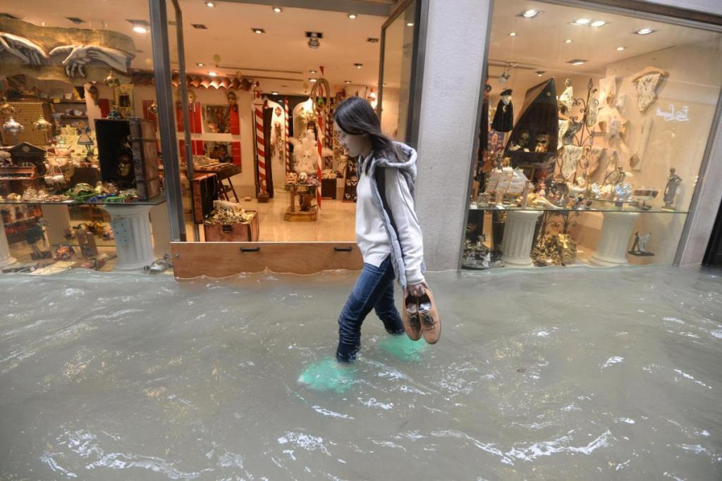 A woman walks in a flooded street of Venice, Italy, on Monday, as 70 percent of the lagoon city was flooded by waters rising more than five feet above sea level, according to city officials.