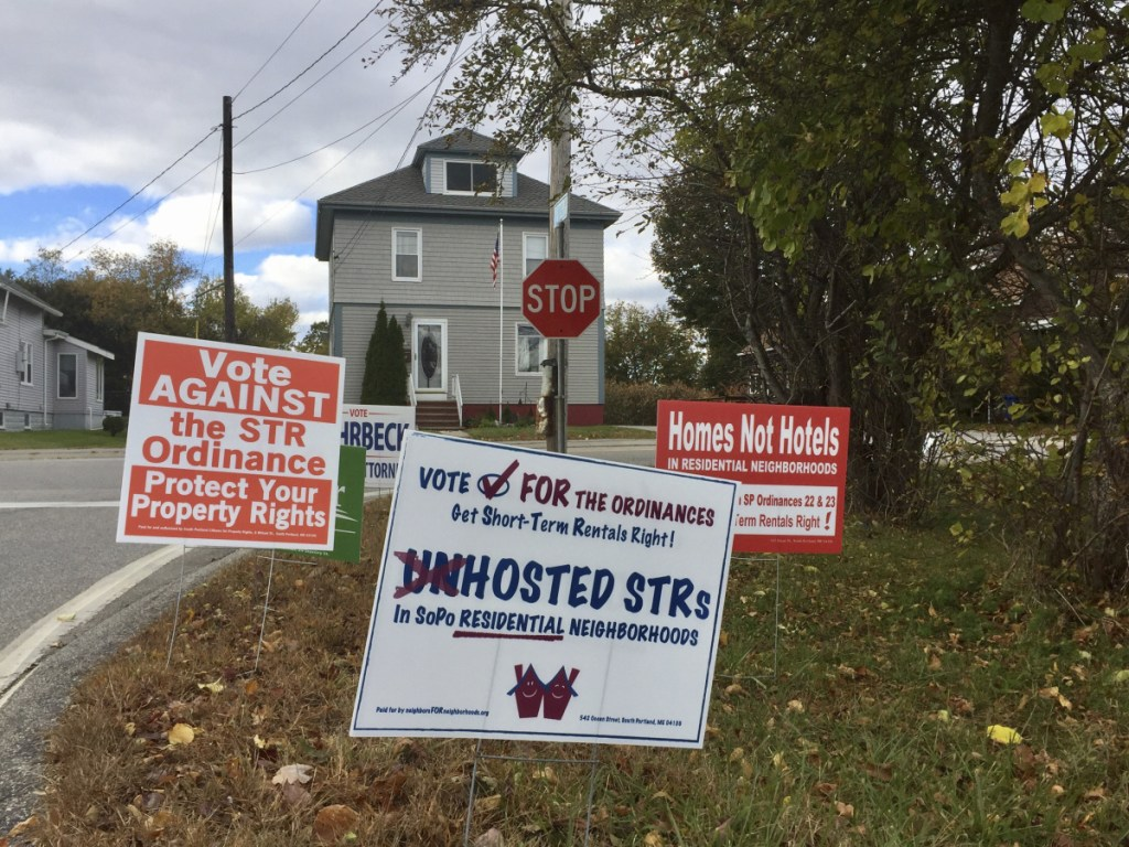 Campaign signs at Nutter Road and Evans Street in South Portland urge voters to cast their ballots either for or against controversial short-term rental regulations that the City Council approved in July.
