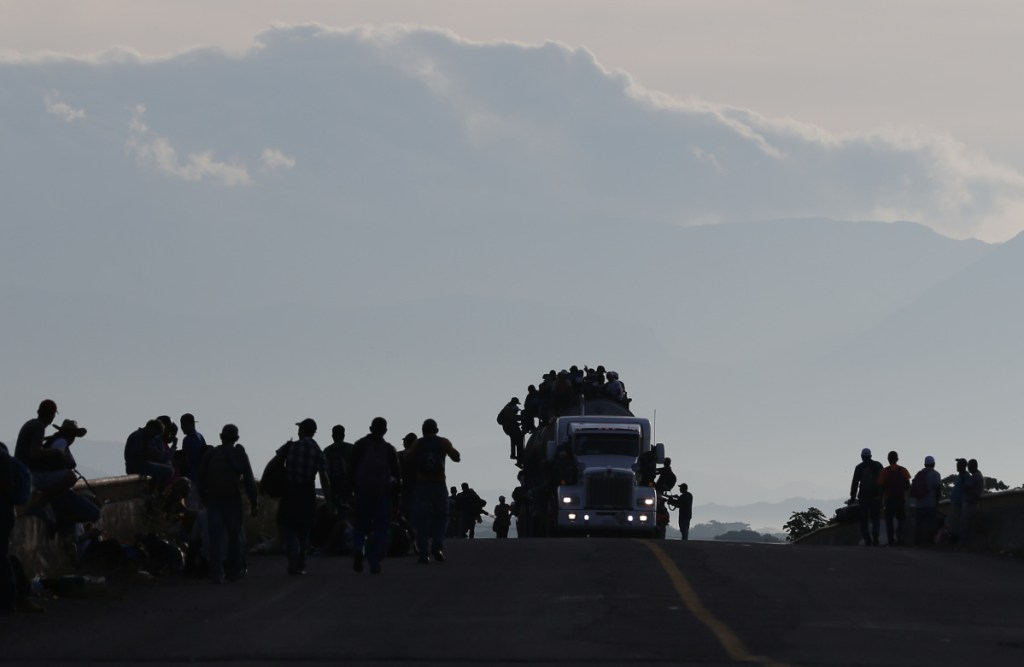 Migrants crowd atop a tanker truck while others walk or wait for rides in Niltepec, Mexico, on Tuesday.