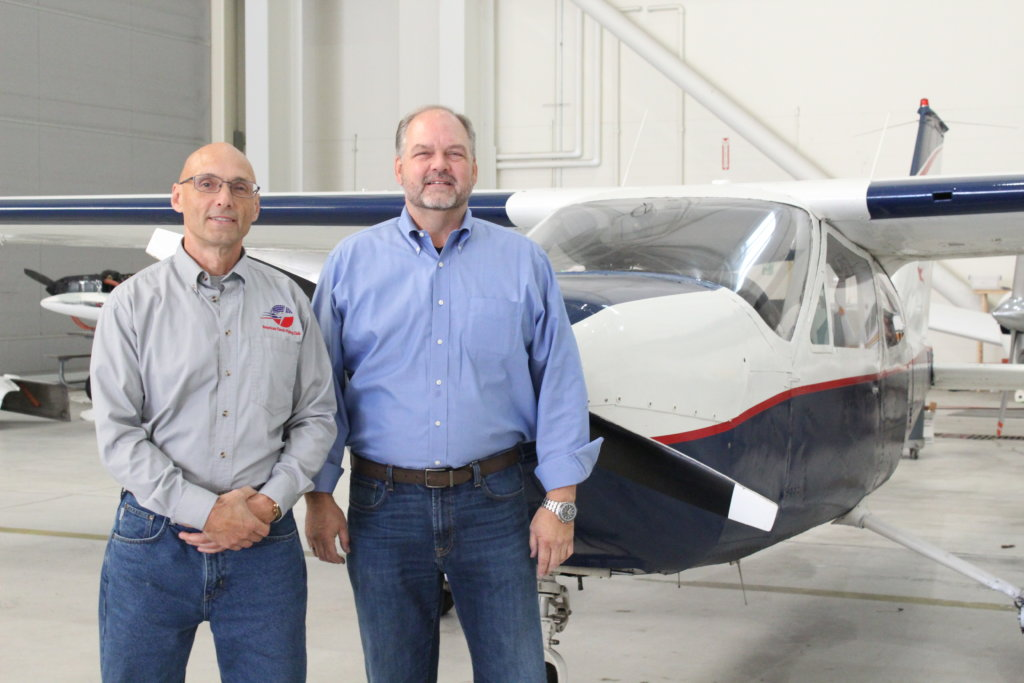"""John Favreau, left, and David Keen of American Classic Flying Club stand with a Cesna Cardinal 177. Keen, who owns American Classic Aviation, said he and his instructors want to reach out to more young people to get them interested in flying careers. """"It's a growth industry."""""""