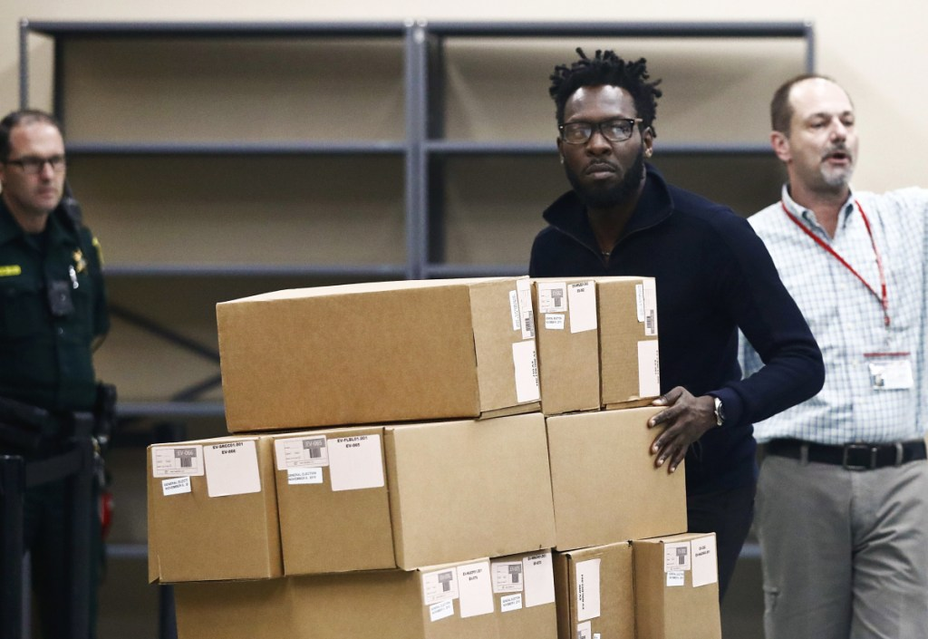 Elections officials move ballot boxes to be counted at the Broward County supervisor of elections office during a recount on Sunday in Lauderhill, Florida.