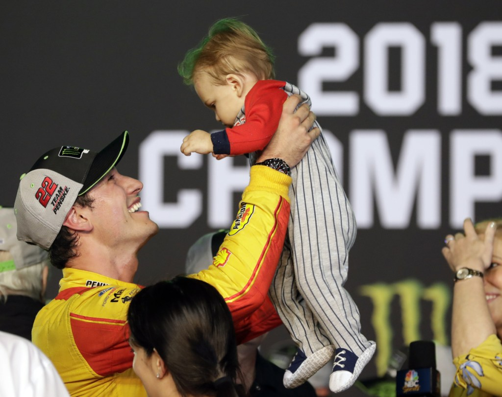 Joey Logano holds his son, Hudson, after winning his first NASCAR Cup Series championship with a victory Sunday at Homestead-Miami Speedway.
