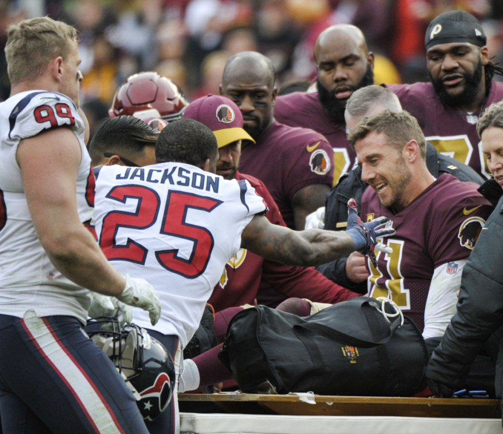 Washington quarterback Alex Smith is consoled by Kareem Jackson of the Texans after his season-ending injury Sunday.