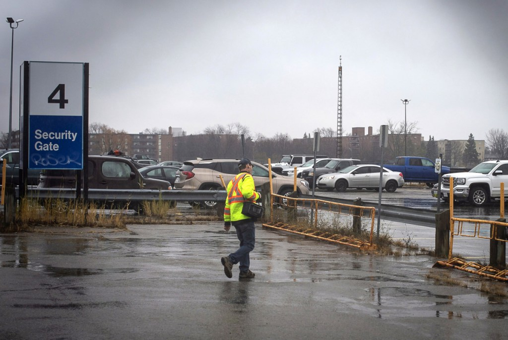 A worker leaves Oshawa's General Motors plant Monday. General Motors will lay off thousands of factory and white-collar workers in North America and put five plants up for possible closure as it restructures to cut costs and focus more on autonomous and electric vehicles. General Motors is closing the Oshawa plant.