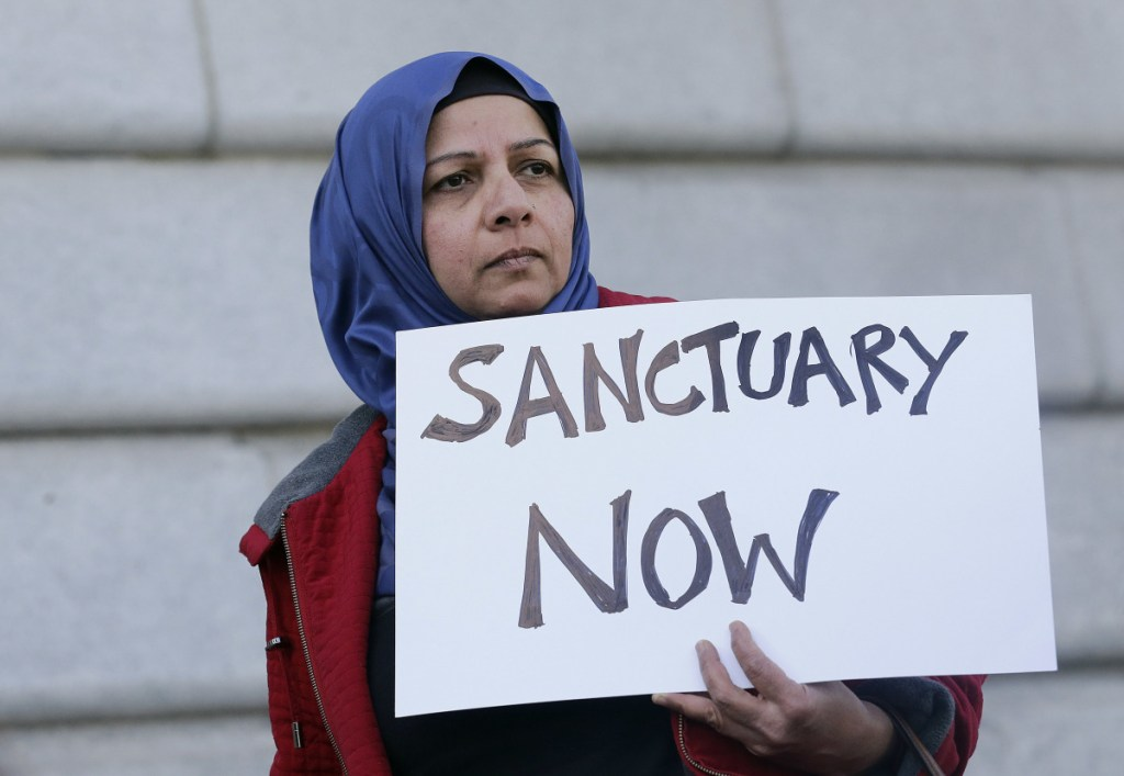 """A woman holds a sign at a rally outside of City Hall in San Francisco in 2017. The Trump administration can't withhold over $29 million from six states and New York City in a clash over their immigration policies as """"sanctuary"""" jurisdictions, a federal judge said Friday."""