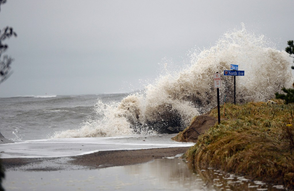 Waves crash over barriers onto North Avenue at Camp Ellis in Saco on Nov. 27.