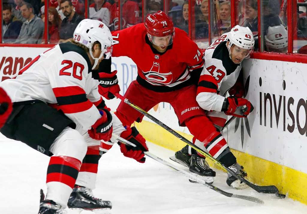 Carolina's Jaccob Slavin (74) battles between New Jersey Devils' Blake Coleman (20) and Brett Seney (43) during the first period of the Hurricanes' 2-1 win Sunday in Raleigh, North Carolina.