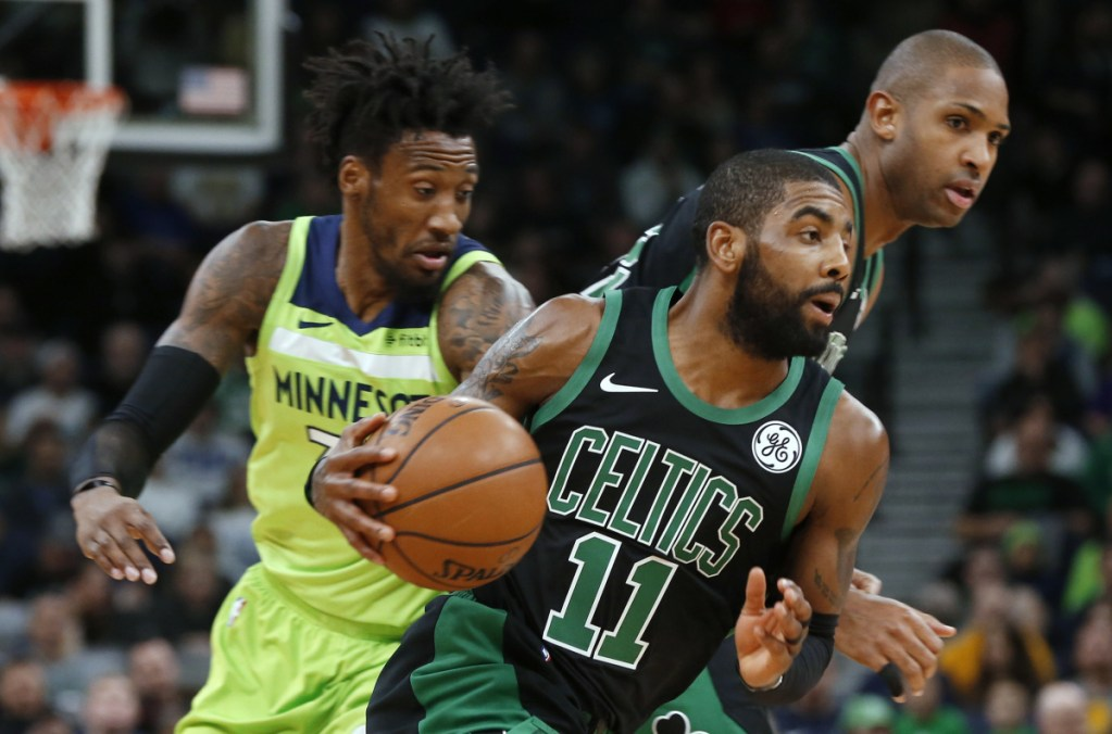 Kyrie Irving drives past Minnesota's Robert Covington during Boston's 118-109 win Saturday night in Minneapolis. Irving finished with 21 points and nine assists.