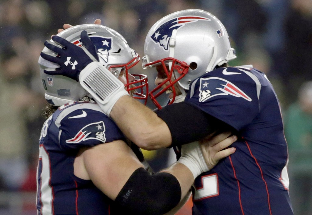 Patriots quarterback Tom Brady, right, celebrates a touchdown run by James Develin, along with center David Andrews, left, during New England's 24-10 win over the Minnesota Vikings on Sunday in Foxborough, Mass.