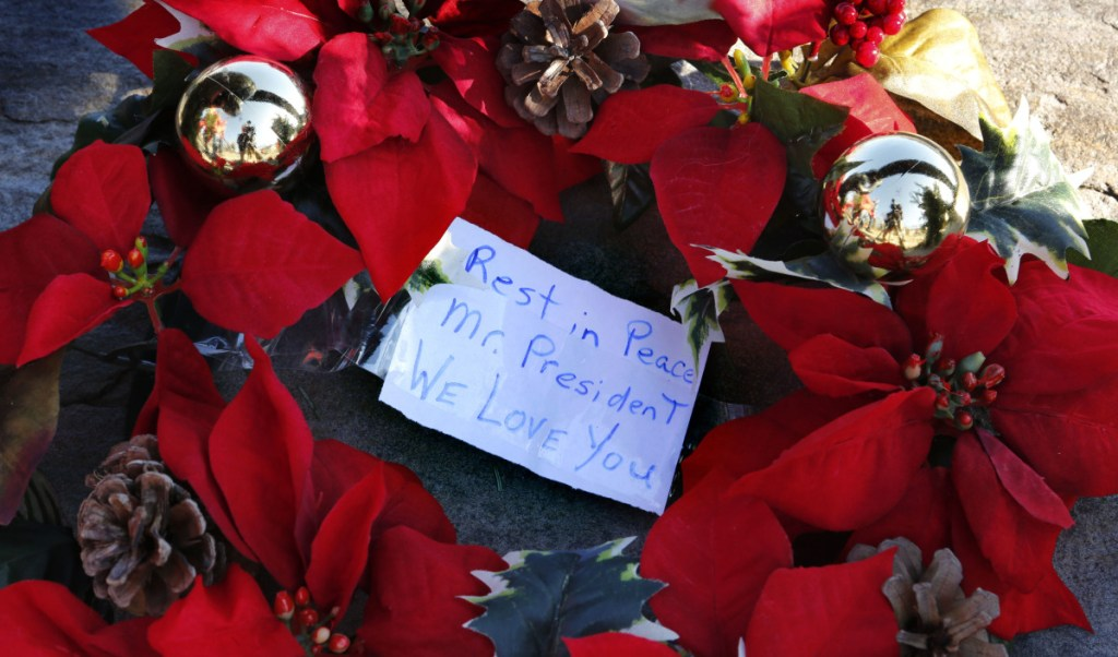 A makeshift memorial across from the Bush summer home in Kennebunkport includes this wreath and note to George H.W. Bush. A reader says he was most impressed by Bush's personal qualities.