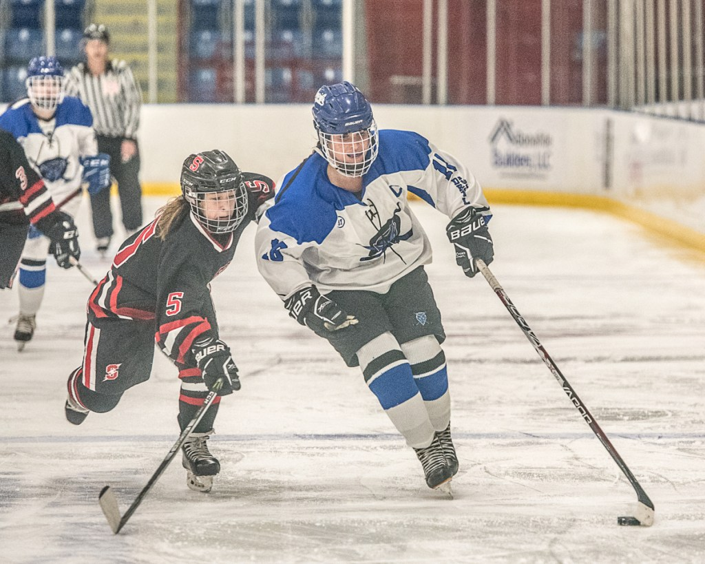 Lewiston's Sara Robert keeps control of the puck as Scarborough's Evelyn Boardman chases behind her during Lewiston's 2-0 win Wednesday night at the Colisee.