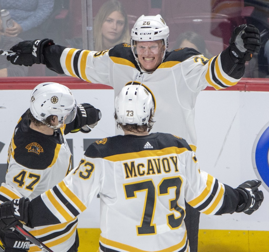 Boston Bruins centre Colby Cave, top, celebrates with teammates Torey Krug, left, and Charlie McAvoy after scoring his first NHL goal on Monday – the Bruins'  second goal in a 4-0 victory over the Canadiens in Montreal.