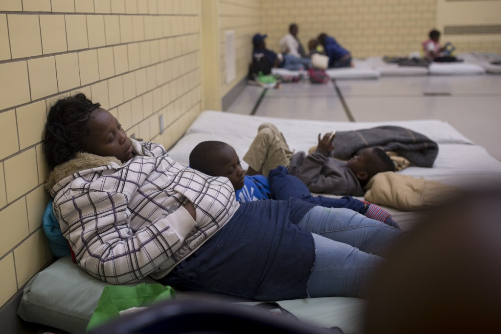 "A mother and son sleep on mats at the Salvation Army gym. Portland's head of social services says the number of asylum seekers is now a ""crisis situation."""