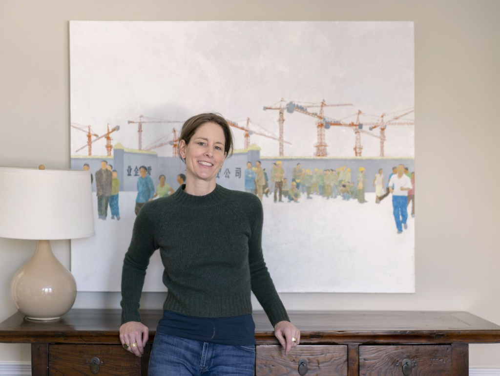Author Susan Conley poses for a photo in her Portland home near a painting of the Beijing waterfront on Tuesday, December 18, 2018. Conley's new novel, Elsey Come Home, is set in Beijing and is getting praise and rave reviews.