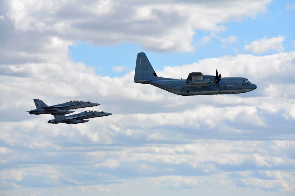 Two U.S. Marine Corps F/A-18 Hornets and a KC-130J Hercules fly during a demonstration in September.