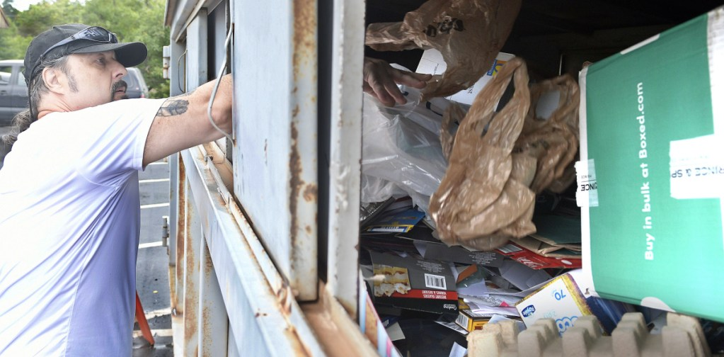 Stephen Mingo recycles items in September at a city collection bin behind the Buker Community Center in Augusta.