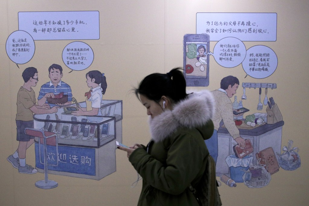 A woman uses an iPhone as she walks by a smartphone ad at a subway station in Beijing on Thursday. Apple's slumping sales suggest that an era of increasing smartphone sales could be ending. Falling sales in China are a main factor, where consumers have a variety of cheaper options.