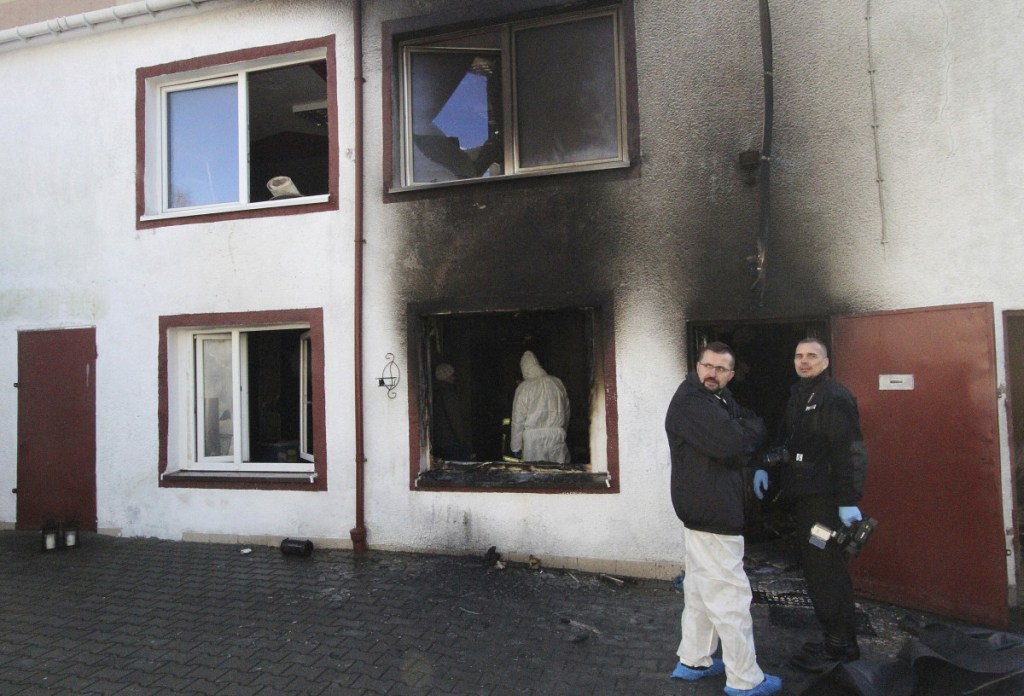 Forensic and other police experts examine the site of a fire adjacent to an escape room in Koszalin, Poland, on Saturday.The fire killed five teenage girls locked inside the escape room and injured a man.