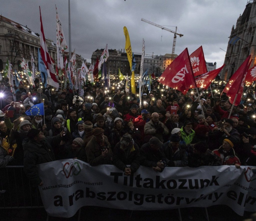 """Anti-government demonstrators carry a banner reading """"We protest against the slave bill"""" as they protest in front of the Parliament building at Kossuth Square in Budapest, Hungary, on Saturday."""