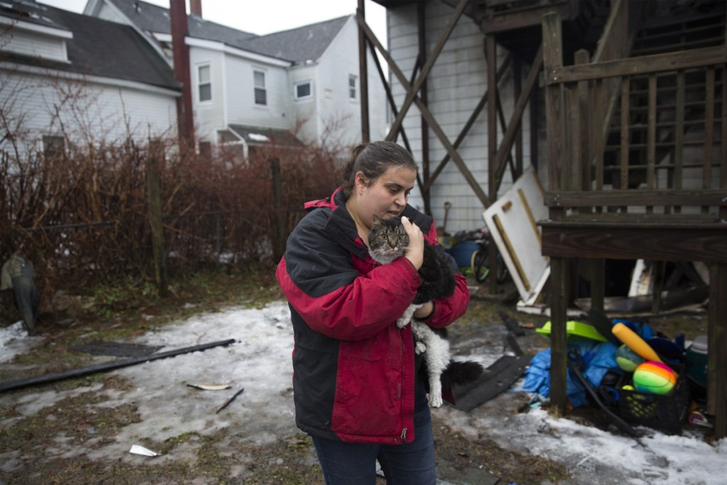 """Jolean Beane carries her sister-in-law's cat Jax back to her car after she caught him outside of the apartment building that caught fire on Swett Street in the early morning on Wednesday, January 9, 2019. Bean said her sister-in-law's family escaped the fire and left the backdoor open as they left. They didn't know what happened to their cat Jax. Beane spent the morning looking for him and finally found him as he ran back to his home. """"We didn't think there was any way the cat got out,"""" Beane said. """"The kids will be so happy."""""""