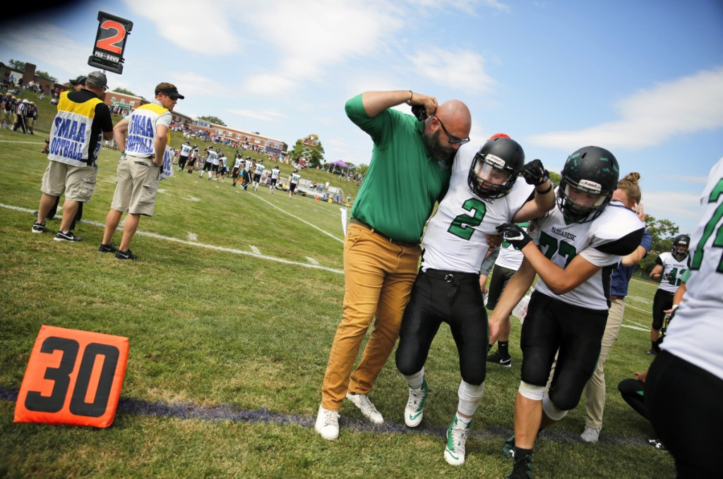 "Massabesic's assistant coach Ethan Magill and teammate Robert Woods help junior Owen Roberts off the field last season after he was hurt in a game against Cheverus in Portland. Maine does not require medical coverage in ""collision"" sports."