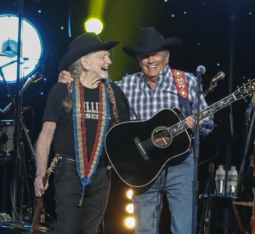 """Willie Nelson, left, and George Strait perform at """"Willie: Life & Songs Of An American Outlaw"""" at Bridgestone Arena on Saturday in Nashville, Tenn."""