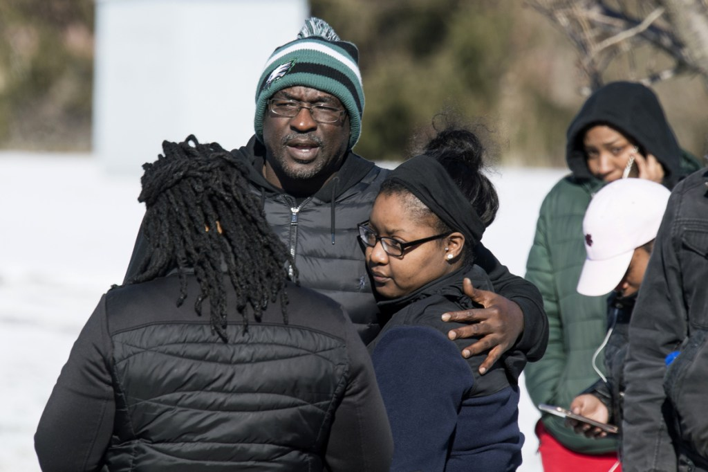 People stand outside the UPS building in Logan Township, N.J., where police say William Owens, 39, held two women hostage Monday. Police shot Owens as he and the women left the building.