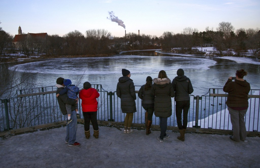"""People gather to watch the ice disk on Jan. 17. The natural phenomenon has been a boon for businesses in Westbrook, where one bar has named a cocktail the """"Ice Disk Cosmo."""""""