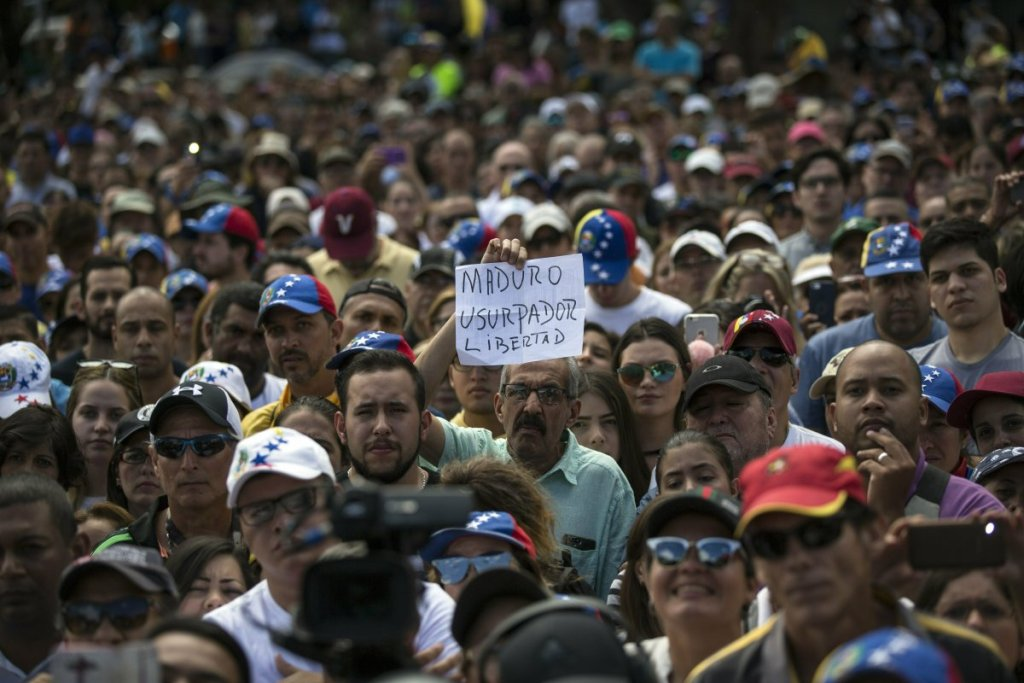 """A man holds a sign with a message that reads in Spanish: """"Maduro, Usurper. Freedom"""" during an opposition rally in Las Mercedes neighborhood of Caracas, Venezuela, on Saturday."""