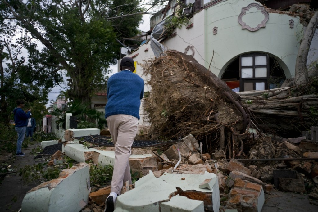 A man takes pictures of the disaster left behind by a tornado in Havana, Cuba, Monday, Jan. 28, 2019. A tornado and pounding rains smashed into the eastern part of Cuba's capital overnight, toppling trees, bending power poles and flinging shards of metal roofing through the air as the storm cut a path of destruction across eastern Havana. (AP Photo/Ramon Espinosa)