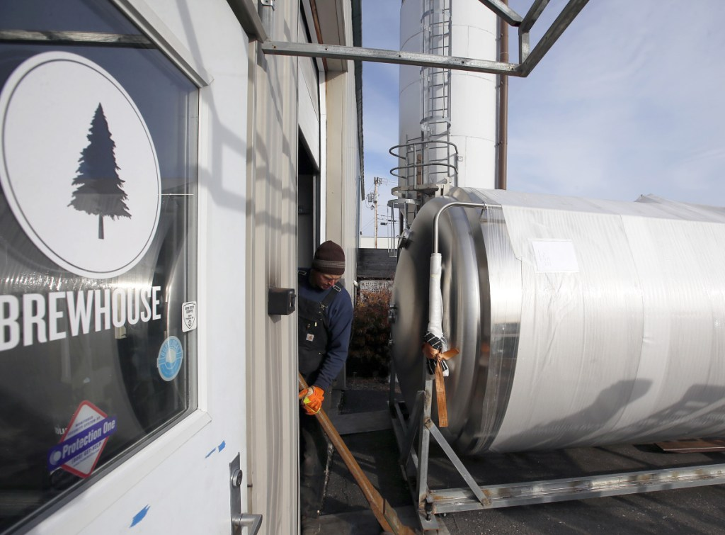 Cote Crane & Rigging foreman Brian Bosse prepares to guide a 2,500-gallon fermenting tank into Lone Pine Brewing Co.'s Gorham facility on Tuesday.