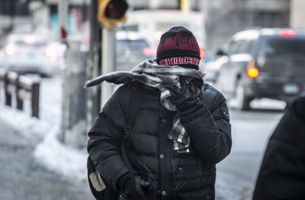 A commuter heads for work early Wednesday in brutally cold Chicago. Meanwhile, Australia is experiencing all-time record heat. It's important to take the whole Earth into account – not just one area, experts say.