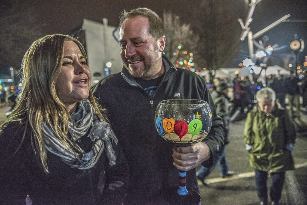 Heather Martel and Rodney Robichaud listen to a band playing on the stage at Auburn's New Year's Eve celebration on Monday.