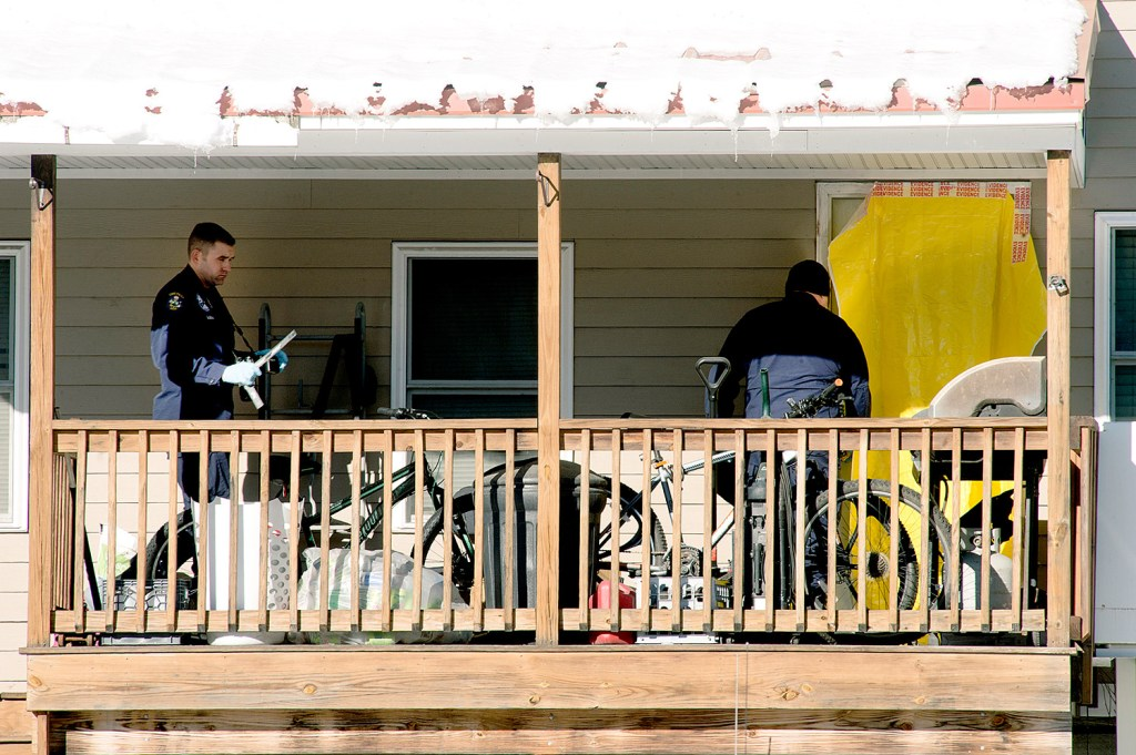 Maine State Police evidence technicians enter the apartment on Wednesday where a man and a woman were found dead in South Paris. Their children, a 2-month-old infant and an 8-year-old, were placed in the care of the Maine Department of Health and Human Services.