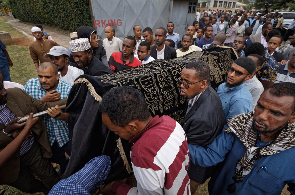 Mourners carry the body of Feisal Ahmed, who was killed with his colleague Abdalla Dahir in Tuesday's attack, as they leave a mosque and head to the funerals in Nairobi, Kenya, on Wednesday. The two were killed by Islamic extremist gunmen who attacked a luxury hotel and shopping complex.