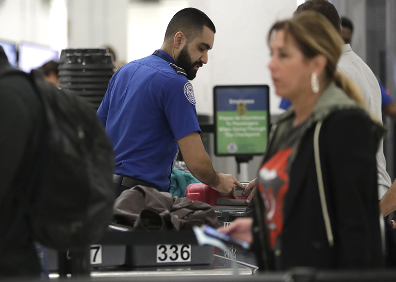 A Transportation Security Administration officer works at a checkpoint at Miami International Airpor on Jan. 6.