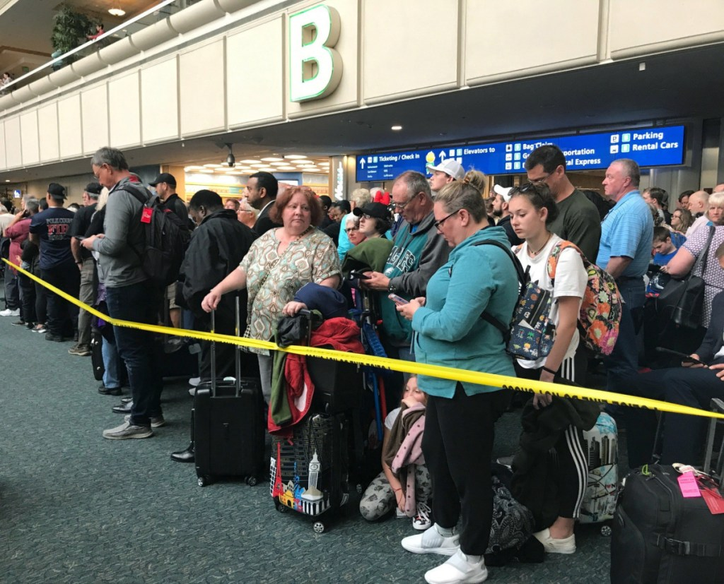 People wait to get through security at the Orlando International Airport following the death of a man who jumped from a balcony. Passengers on shuttles to gates at Florida's busiest airport had to be brought back for a second screening, bringing security checkpoints to a temporary standstill.  .