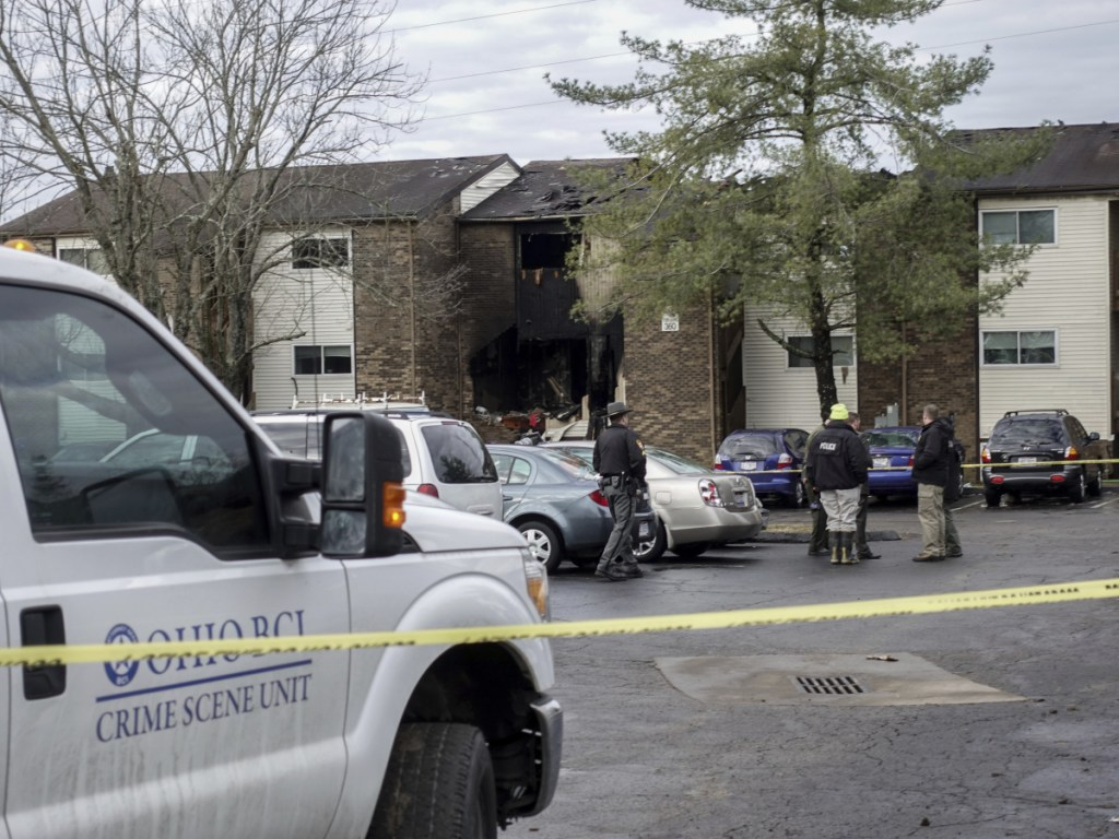 Authorities stand outside the Royal Oaks Apartments in Pierce Township, Ohio, on Sunday.