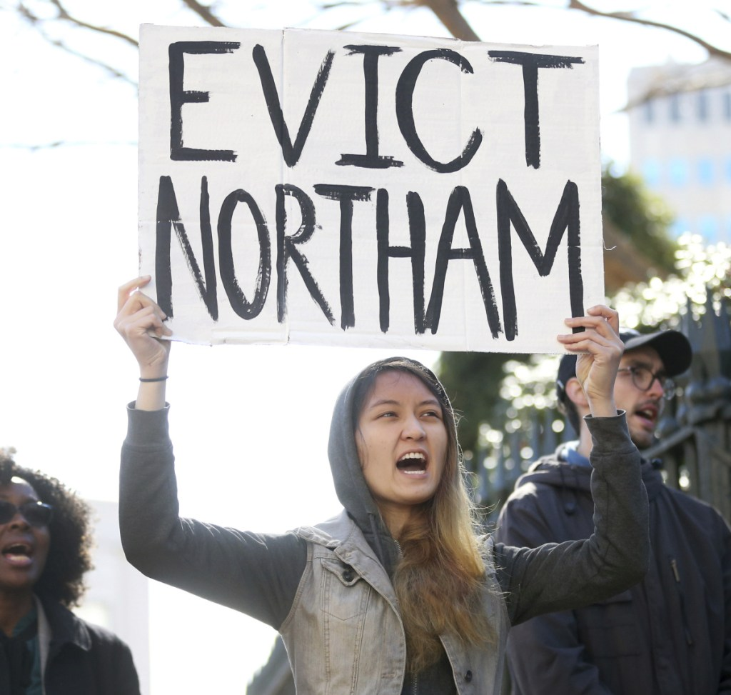 Geraldine Mabagos holds a sign during a protest in Richmond calling for Gov. Ralph Northam to resign on Monday. Northam has rebuffed widespread calls for his resignation after a racist photo surfaced Friday in his 1984 medical school yearbook page.