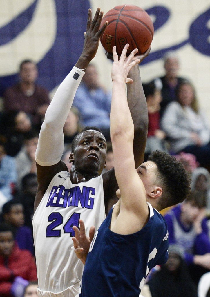 Ben Onek of Deering, left, elevates to get a shot over Jeremiah Alado of Portland during Thursday's game in Portland. Deering won to finish the regular season at 12-6.
