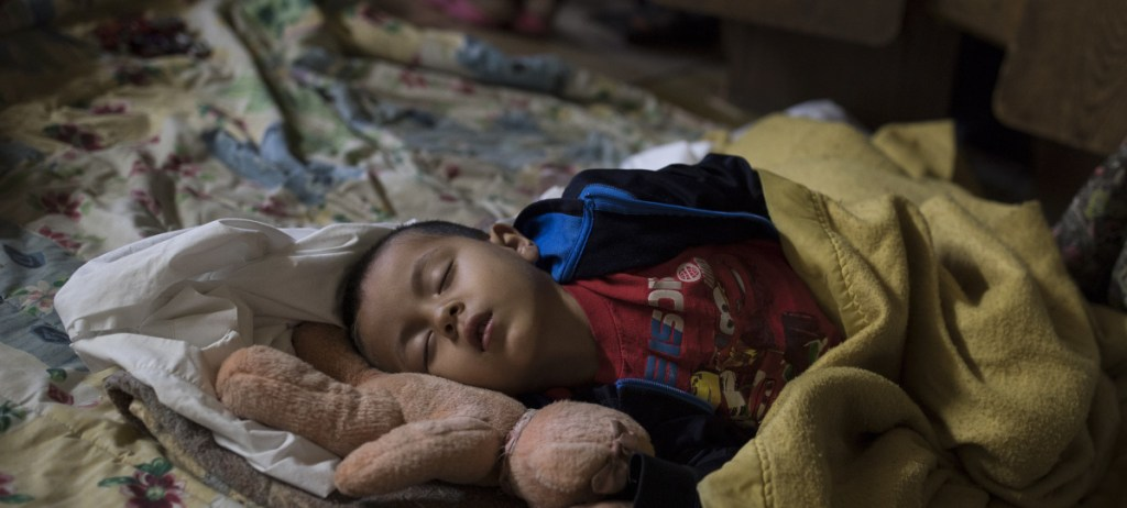 A Central American child who is traveling with a caravan of migrants sleeps at a shelter in Tijuana, Mexico, knowing  that they face possible separation from their children and detention.