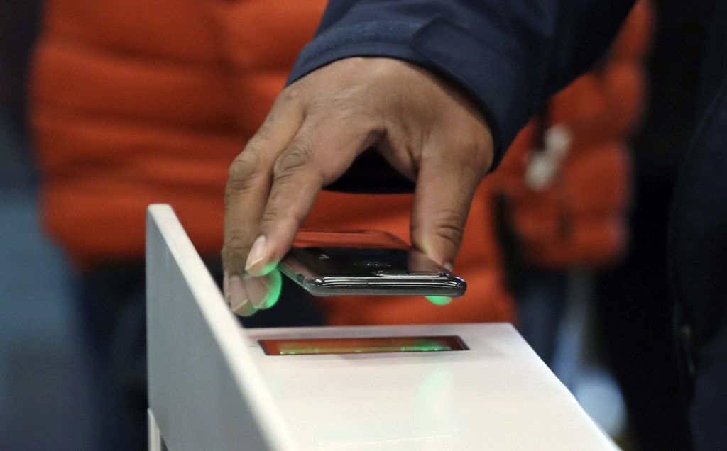 A shopper scans his cellphone app while entering an Amazon Go store last year in Seattle, where transactions are all digital.