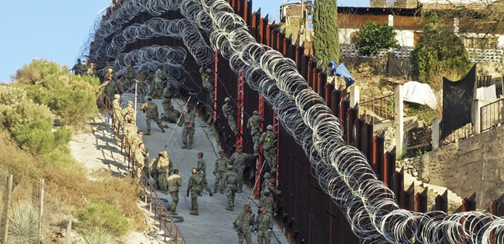 U.S. troops add concertina wire to the border fence in downtown Nogales, Ariz., on Feb. 2. Crime is down in border cities, as are estimates of the number of people entering the U.S. illegally.