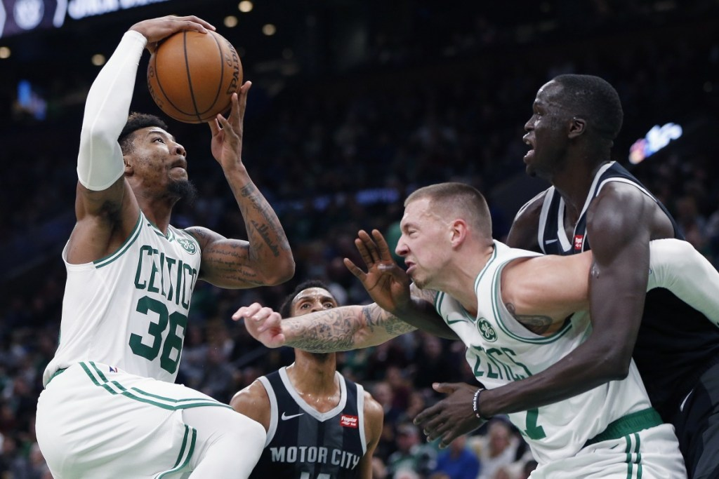 Boston Celtics' Marcus Smart, left, goes up to shoot as Daniel Theis, center, screens Detroit Pistons' Thon Maker, right, during the first half of an NBA basketball game in Boston, Wednesday, Feb. 13, 2019. (AP Photo/Michael Dwyer)
